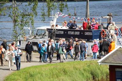 Foto av turistbåten MS Øyeren ved land. Passasjerer i ferd med å gå av båten.