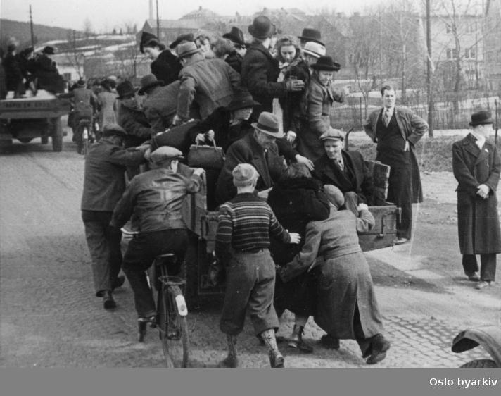 Panikkdagen 10. april etter rykter om bombing av Oslo fra britiske bombefly. Presis klokken 11.30 onsdag 10. april 1940 gikk flyalarmen. Flyktende mennesker til fots, på lastebiler og sykler opp langs Trondheimsveien på Sinsen. I bakgrunnen ses Aker sykehus med område av verdifulle bygninger som Tonsen gård og Sinsen gård. Villabebggelsen i Olav Hegnas vei til høyre. Alle husa (tolv stykker svenskehus) på nordsida av veien blei i 2006 revet på grunn av arbeidet med å bygge ny Ring 3 mellom Ulven og Sinsen.