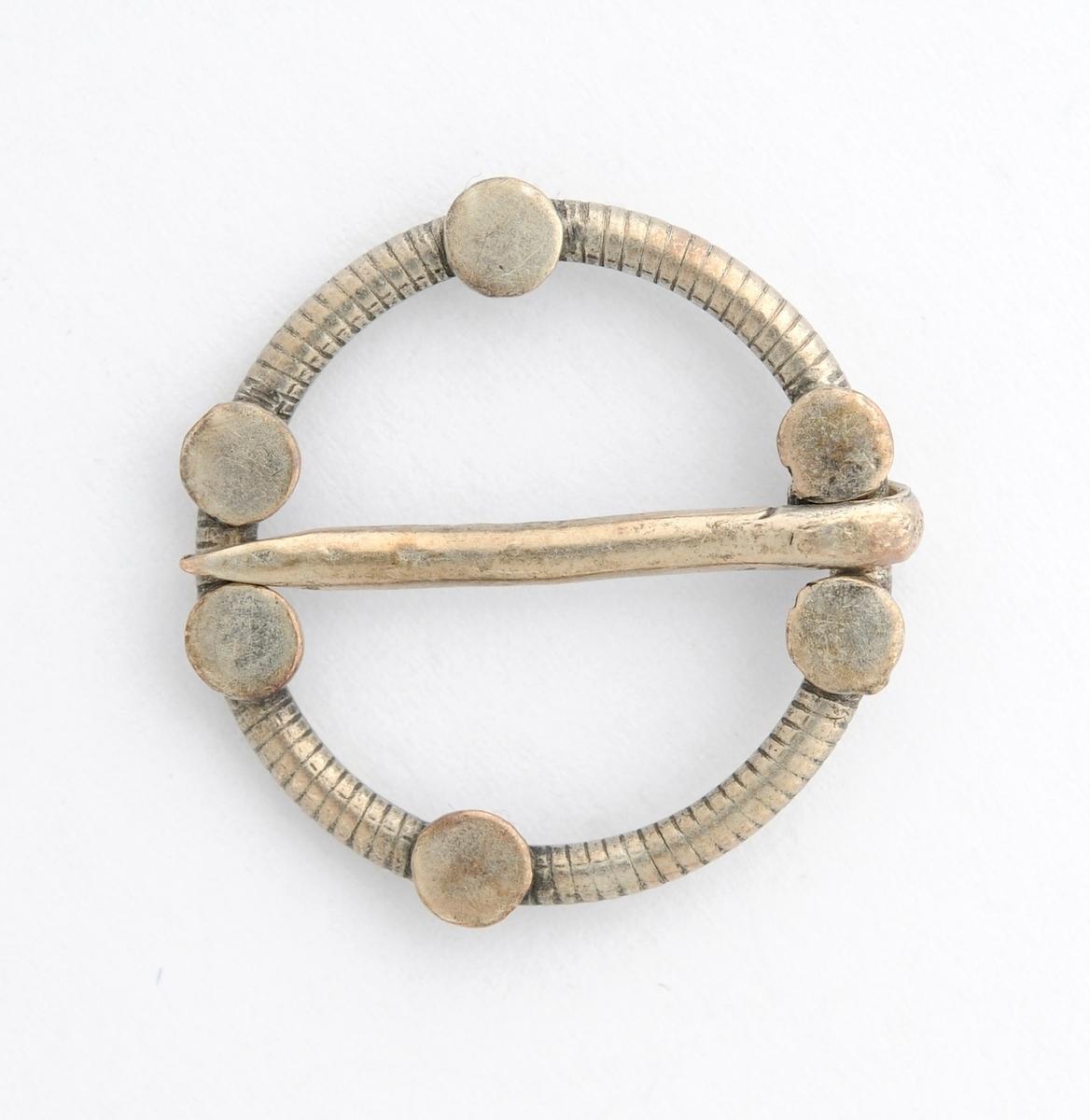 Barnesølje, Rund, støypt ring i sølv (manglar stempel. Pålodda seks små flate rundingar.  Laus tann.