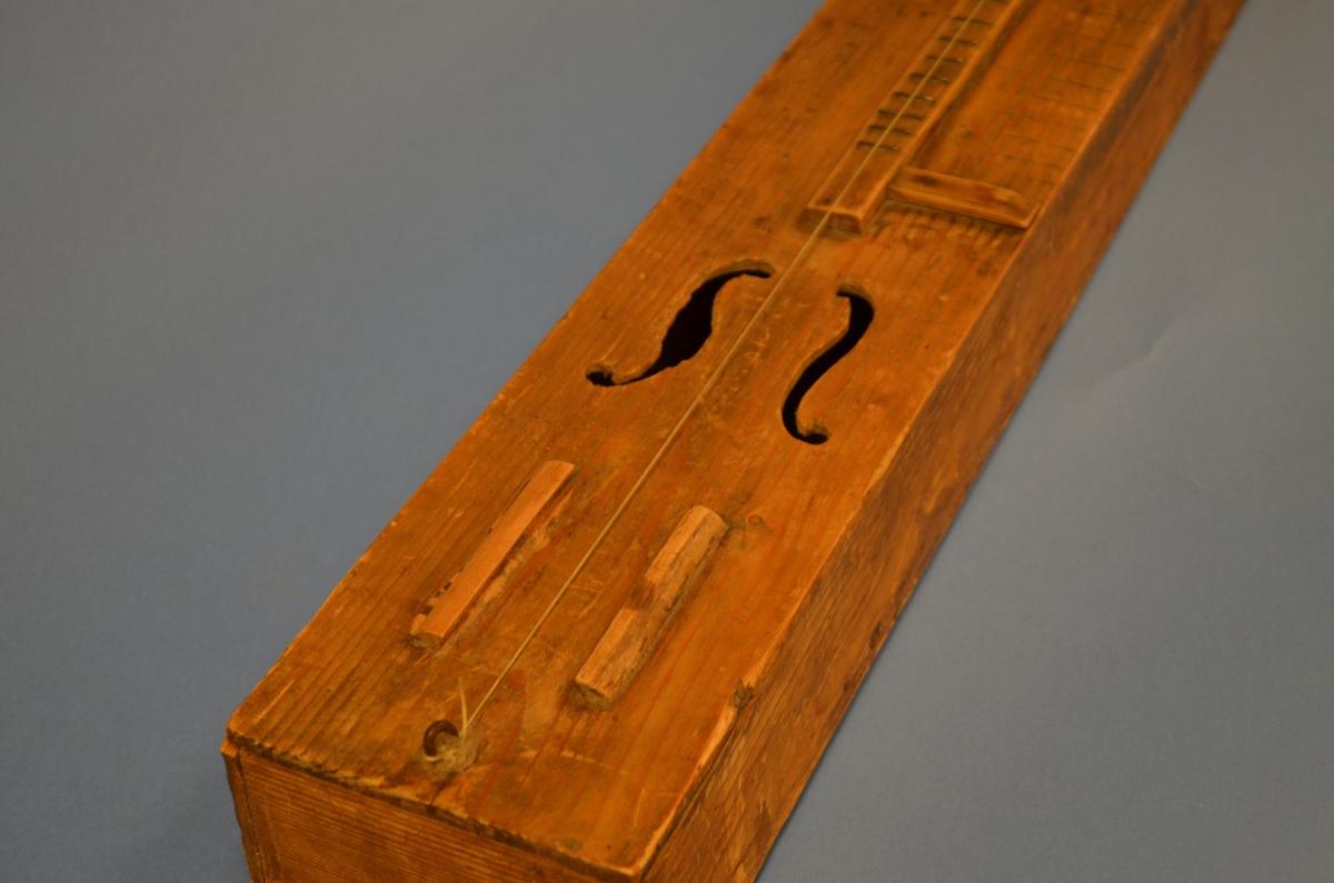 Langsmal instrumentkasse sett saman av separate delar: botn, lok, sargar og tverre endestykke. Sekundært noteband og markeringsstriper i framkant. To s-lydhol, streng og stillarpinne.