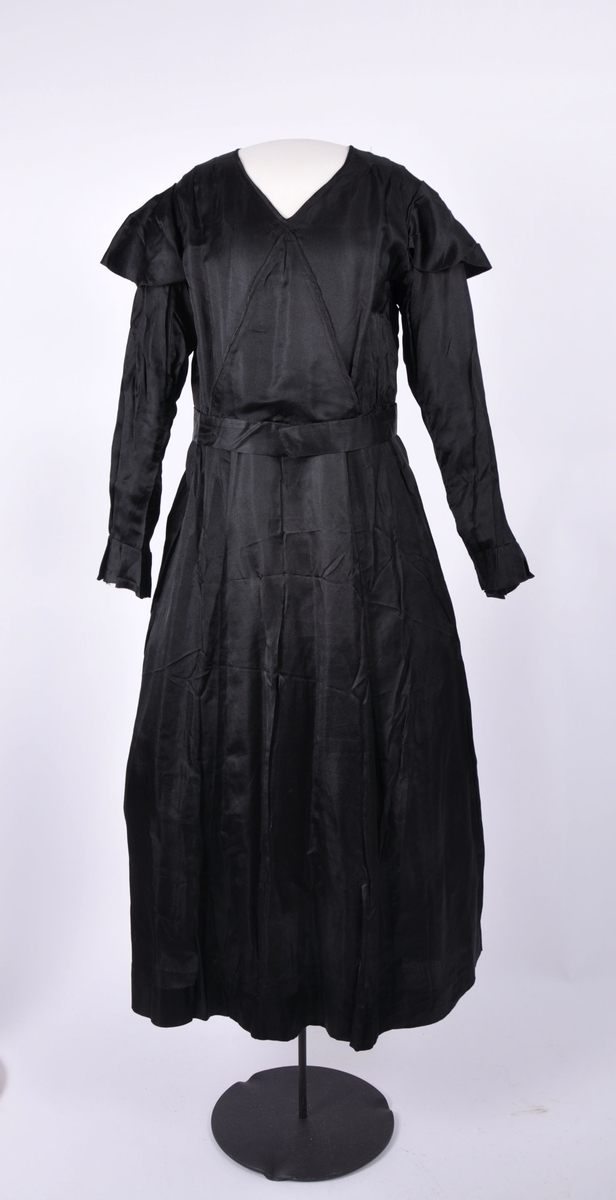 59c943d1 Sort silkekjole med lange ermer. Kappe øverst på hvert erme. Ermene  avsluttes nederst med