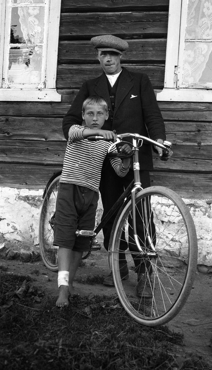 98590d94 En voksen mann og en smågutt med sykkel foran en husvegg. Ingen av de to