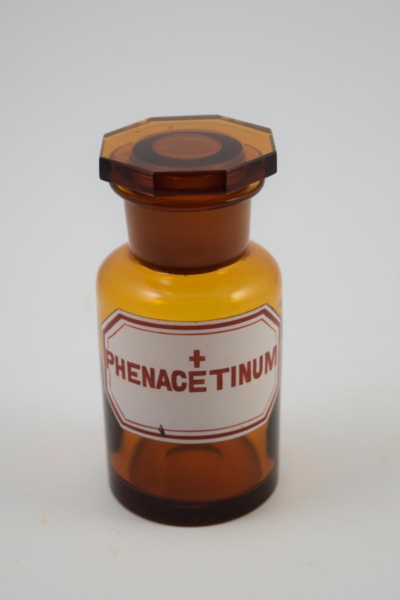 Brun glasskrukke med glasspropp. Hvit etikett med rød skrift. Ett kors betyr at innholdet er giftig. Har inneholdt Phenacetin, som brukes i smertestillende og febernedsettende. Til bruk i legemiddelproduksjon.