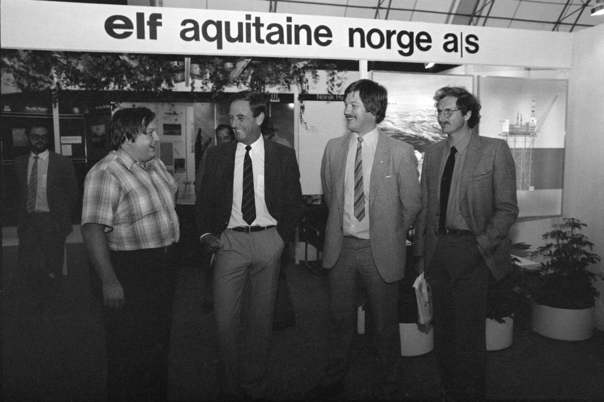 Fire menn foran en messestand (?) for Elf Aquitaine.
