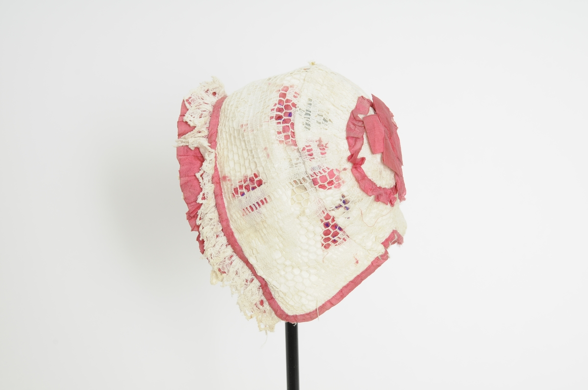 Dåpslue i kvit bomull med påsydde blomster i rosa, grønt og gult, maskinhekla blonder over. Rosa silkeband rund kanten. Foldelagt kant framme med blonde og rosa band.  På baksida rund ring med rosa silkesløyfe.  Fòra med kvitt bomullstøy.