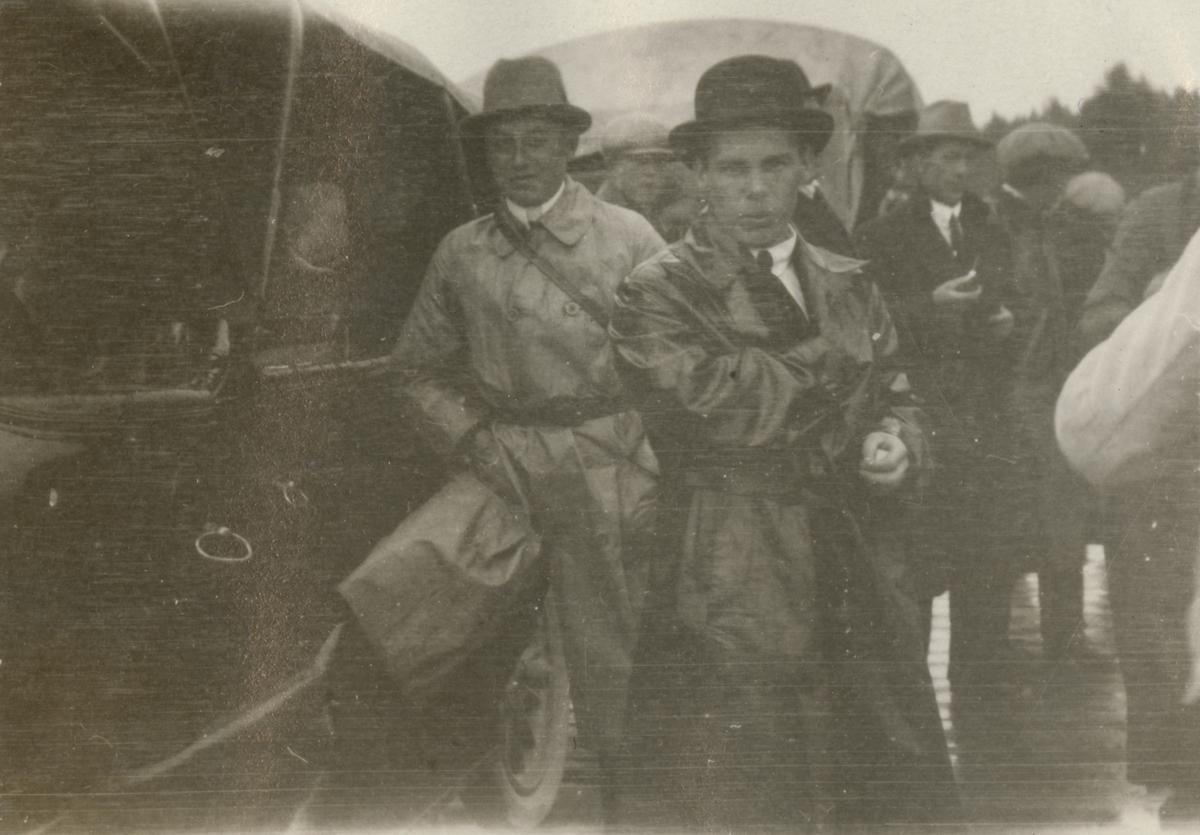 Grupp män samlade vid motorfordon.