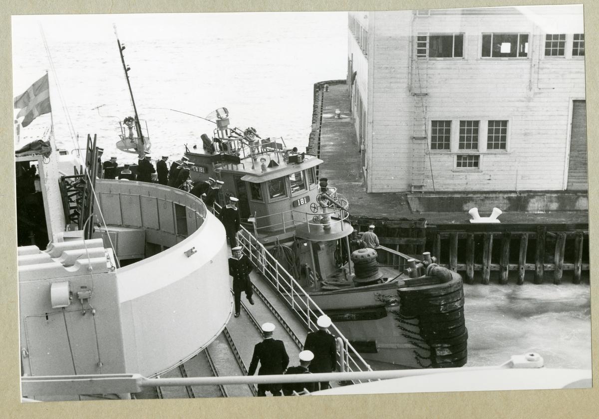 Bilden föreställer en bogserbåt klämd mellan en kajkonstruktion och minfartyget Älvsnabben. På Älvsnabbens däck syns uniformsklädda besättningsmän. Bilden är tagen under minfartygets långresa 1966-1967.