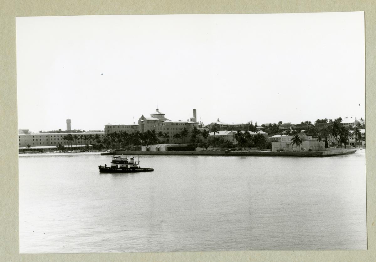 Bilden föreställer en stadsvy av Bahamas huvudstad Nassau med bebyggelse och växtlighet. Framför staden syns ett fartyg. Bilden är tagen under minfartyget Älvsnabbens långresa 1966-1967.