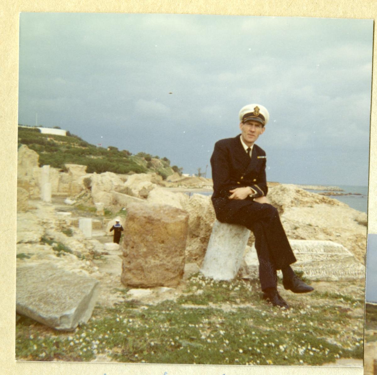 Bilden föreställer Oskar Linde iklädd uniform sittande bland ruinerna av Kartago i samband med minfartyget Älvsnabbens långresa 1966-1967.