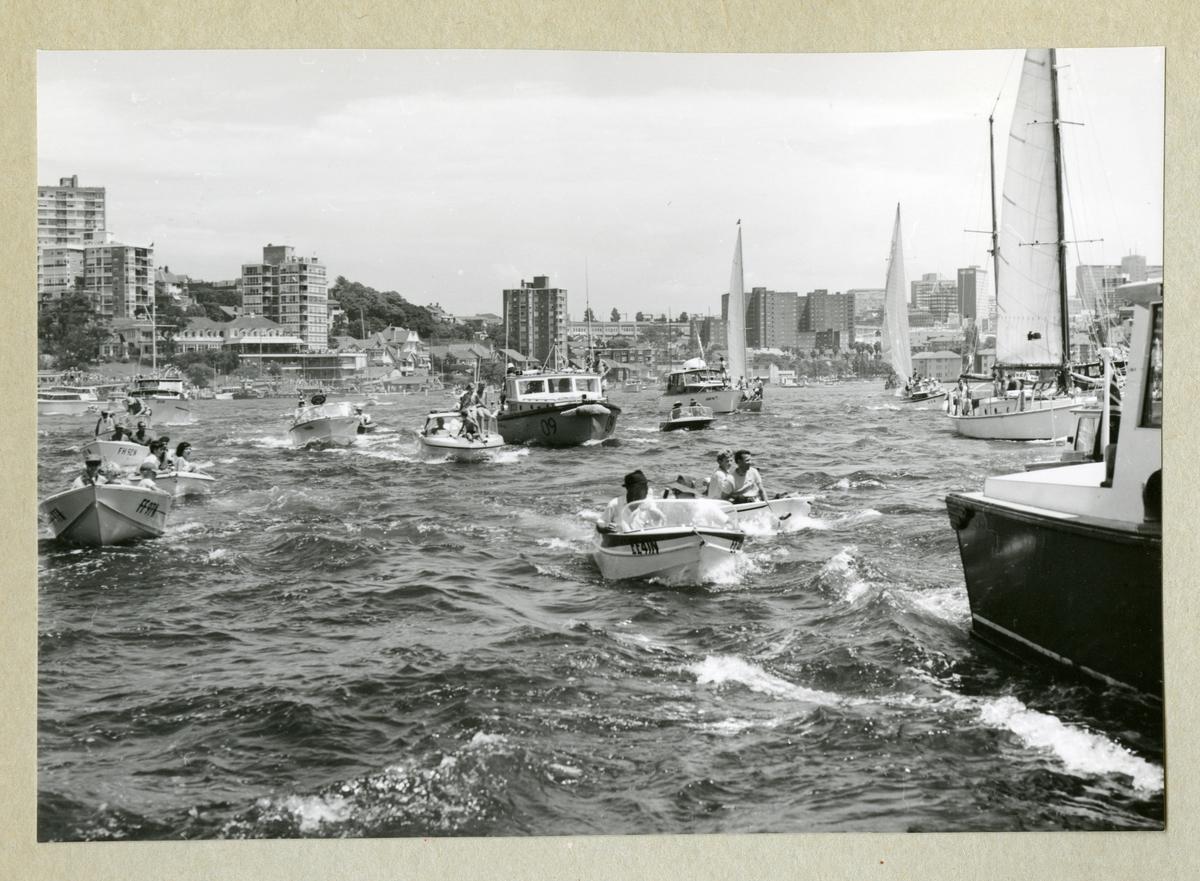 Bilden föreställer en samling av motor- och segelbåtar av olika storlekar. I bakgrunden syns kanten av en kuststad med höghus längs med kustlinjen. Bilden är tagen under minfartyget Älvsnabbens långresa 1966-1967.