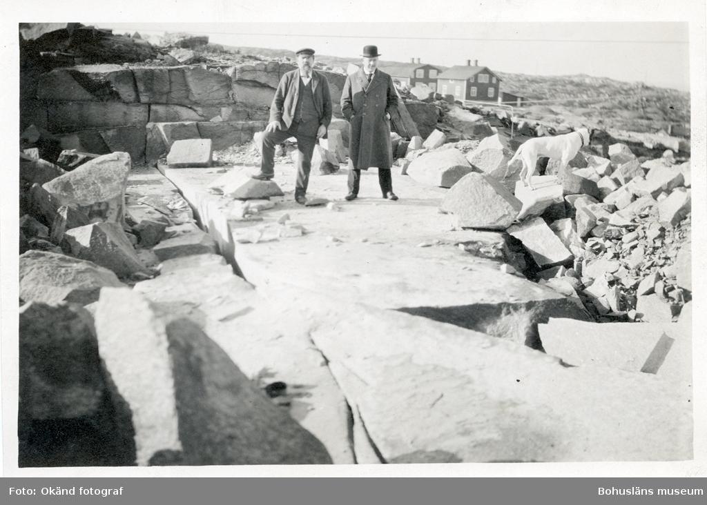 Två män och en hund står bland stenbocken i stenhuggeriet i Rixö