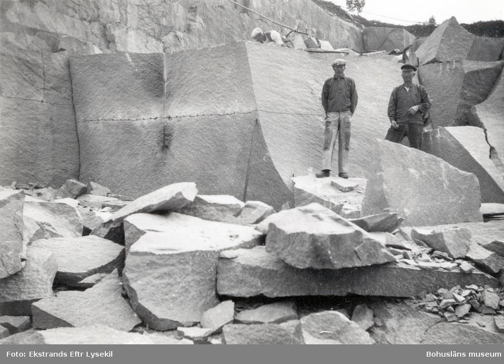 Stenhuggare vid granitblock som sprängts loss från berget