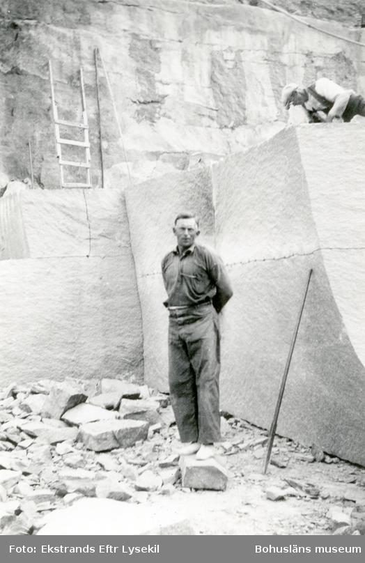 Stenhuggare framför stenblock som sprängts loss