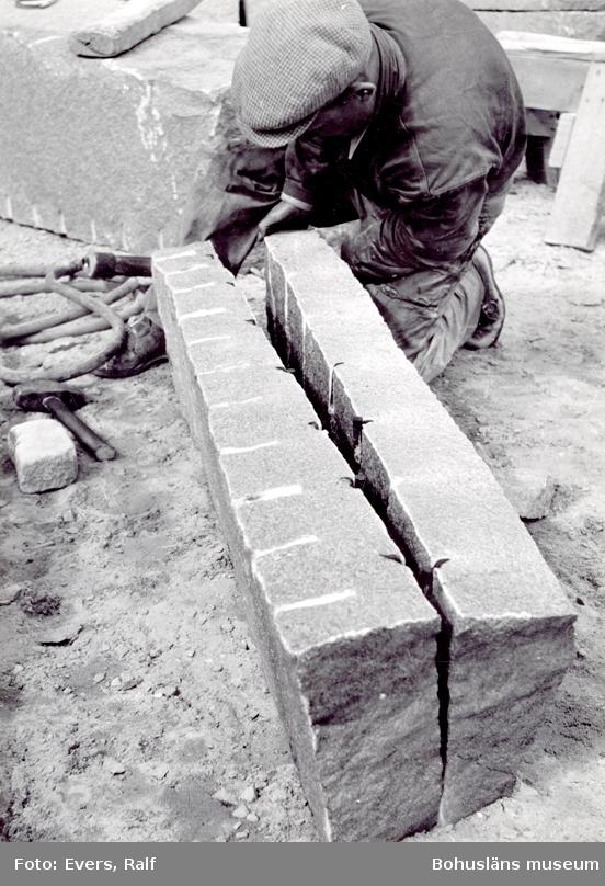 Ett stenblock klyvs längs borrsömmen genom att kilar slås ner i borrhålen