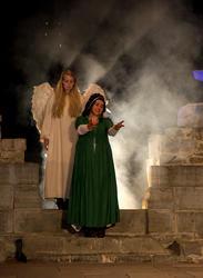 En hvit engel står i en røyksky bak Jomfru Karine som strekker armene fram.