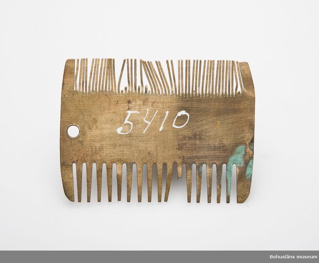 Ur handskrivna katalogen 1957-1958: Kam av mässing Mått: 6,1 x 4,5 cm; m. dubbel tandning, den ena grövre än d. andra. Ärgig, tänder saknas.  Lappkatalog: 94