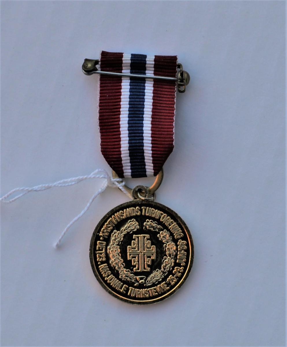 Rund medalje med festebånd i Norges nasjonalfarger.