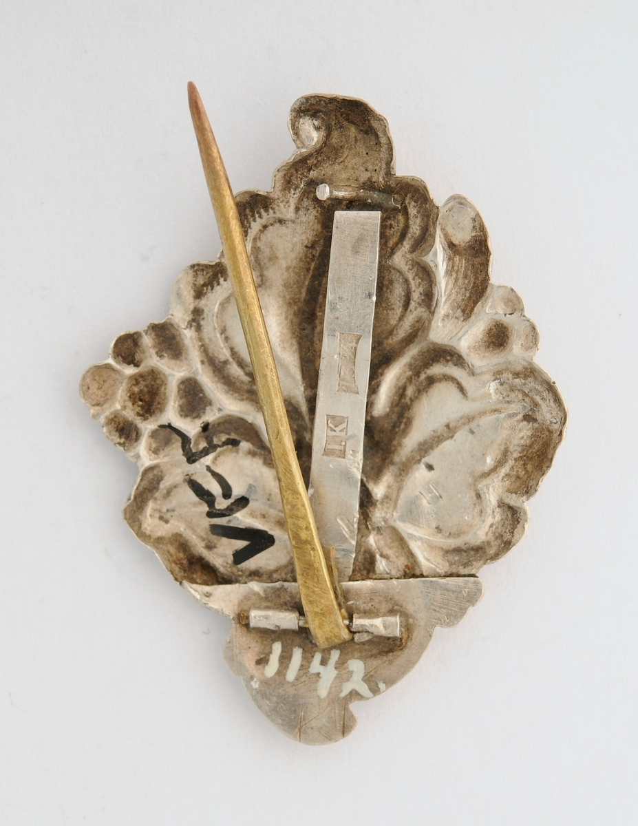 "Sølje, i pressa sylvblikk, forma som eit ""tre flika blad"" (protokoll A 1).  Pålodda nål (i messing) bak, kroken er avbroten. Stempla med I.K og 13 1/4."