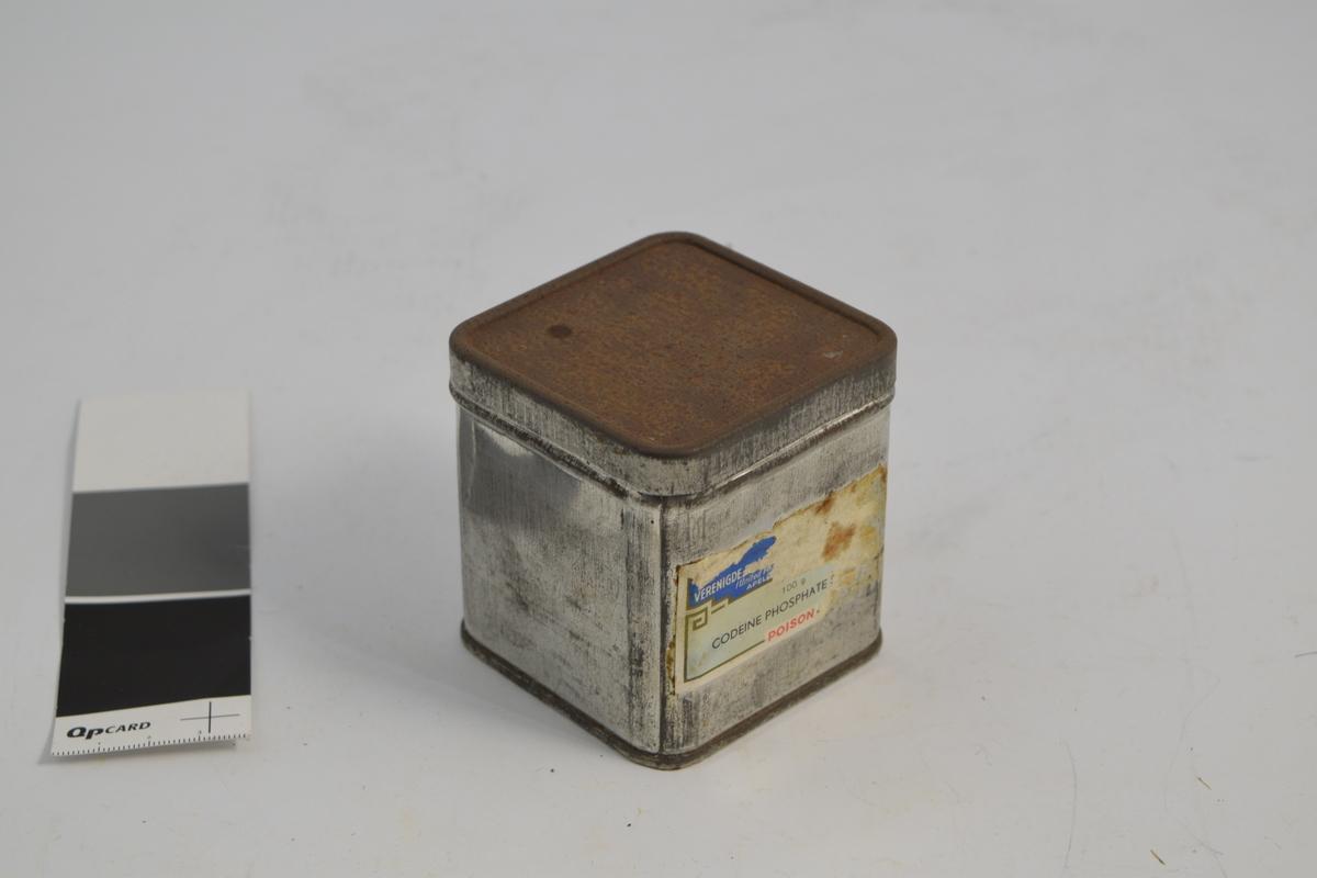 Metallboks firkantet, rektangulær med lokk. Brukt til råvareoppbevaring av Kodein-fosfat, nå tomt. Ved inntak, og nå blir boksen brukt til lagring av apotekfrakk-knapper.