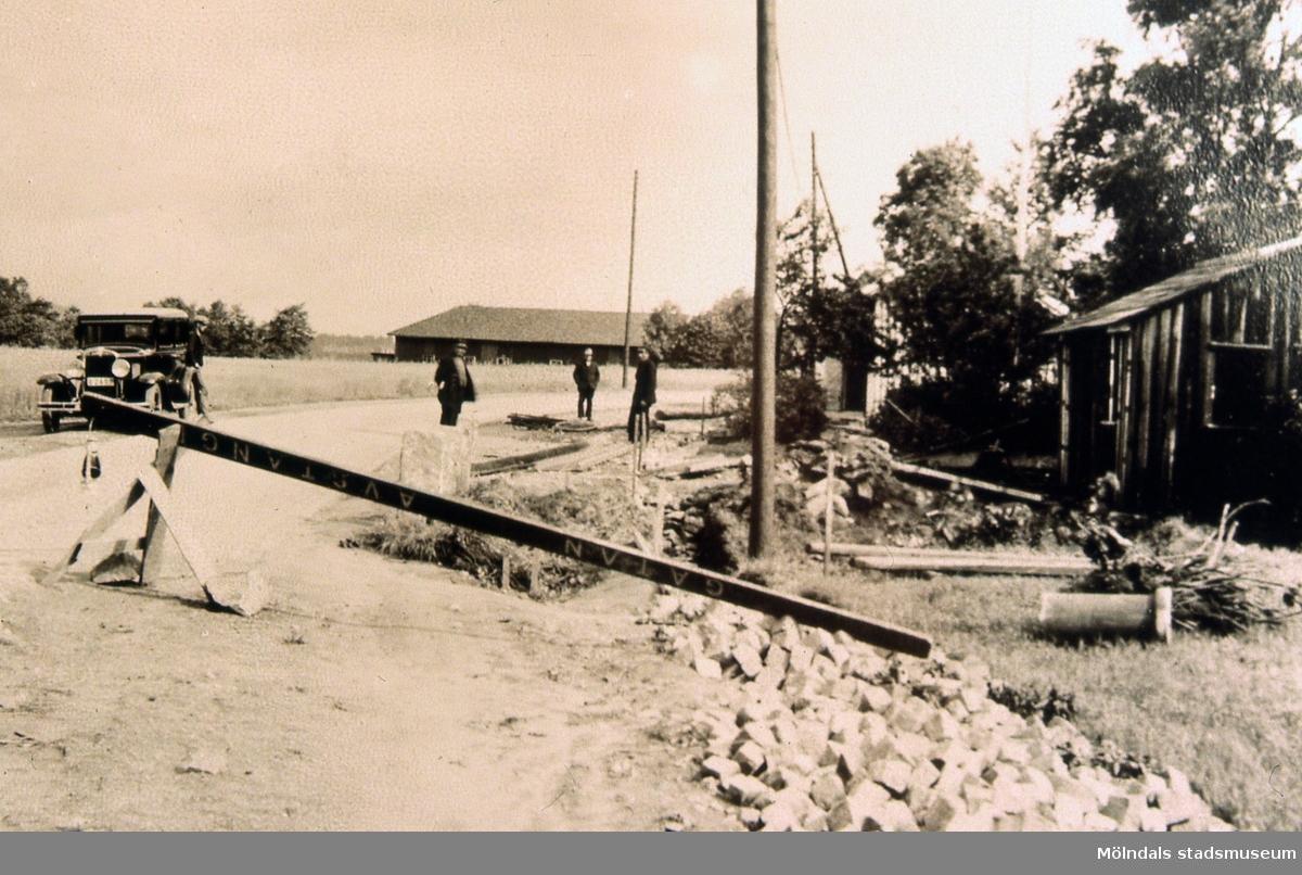 Smedjan vid Kärrabro i Mölndal, troligen år 1932. På vägen utanför står fyra män och en bil vid en vägbom. R 5:24.