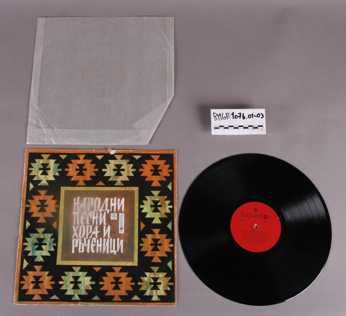 Grammofonplate i svart vinyl med plateomslag av papir. Platen ligger i en plastlomme. Det er påskrift på baksiden av plateomslaget (se bilde).