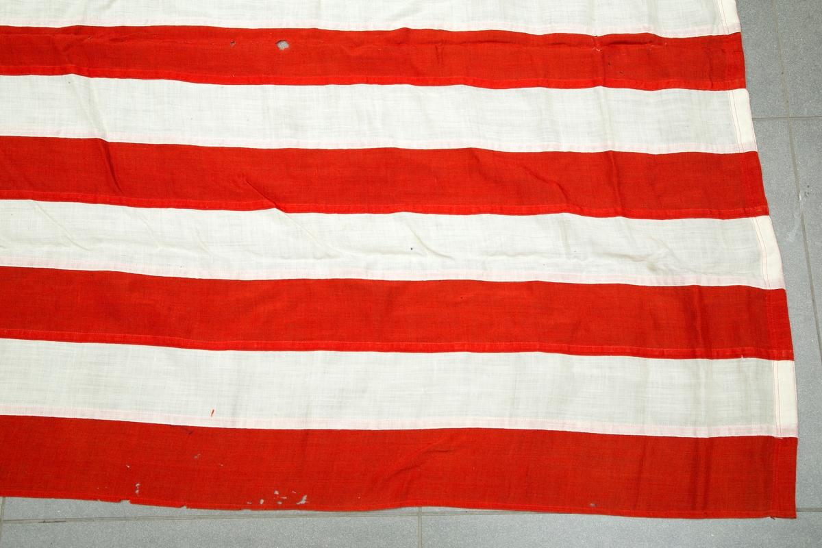 Flaggpose med flagg. A) pose i jute med tau. B) amerikansk flagg.