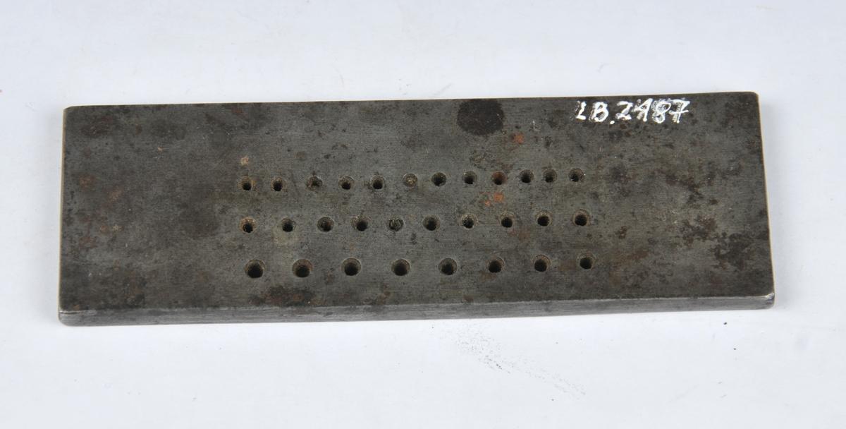 Rektangulært metallstykke med utstansa hol i ulike storleikar.  Tysk fabrikat. 30 hol. Til å trekkje sylvtråd.