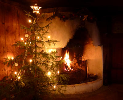 Et juletre med lys, juletrepynt og stjerne i toppen står foran en gammel peis hvor det brenner stemningsfullt.