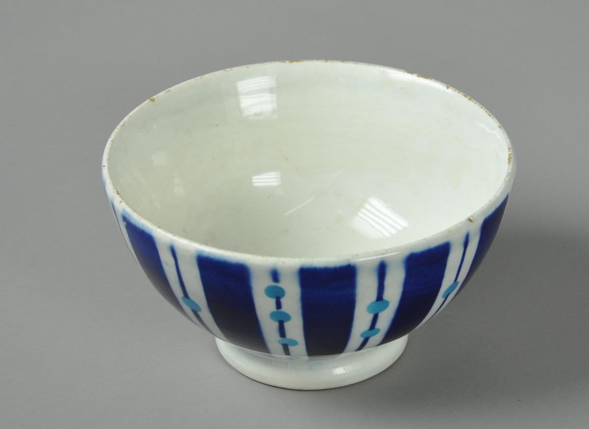 Hvit skål av glassert keramikk, med påmalt dekor. Motiv på malt dekor er striper og sirkler.
