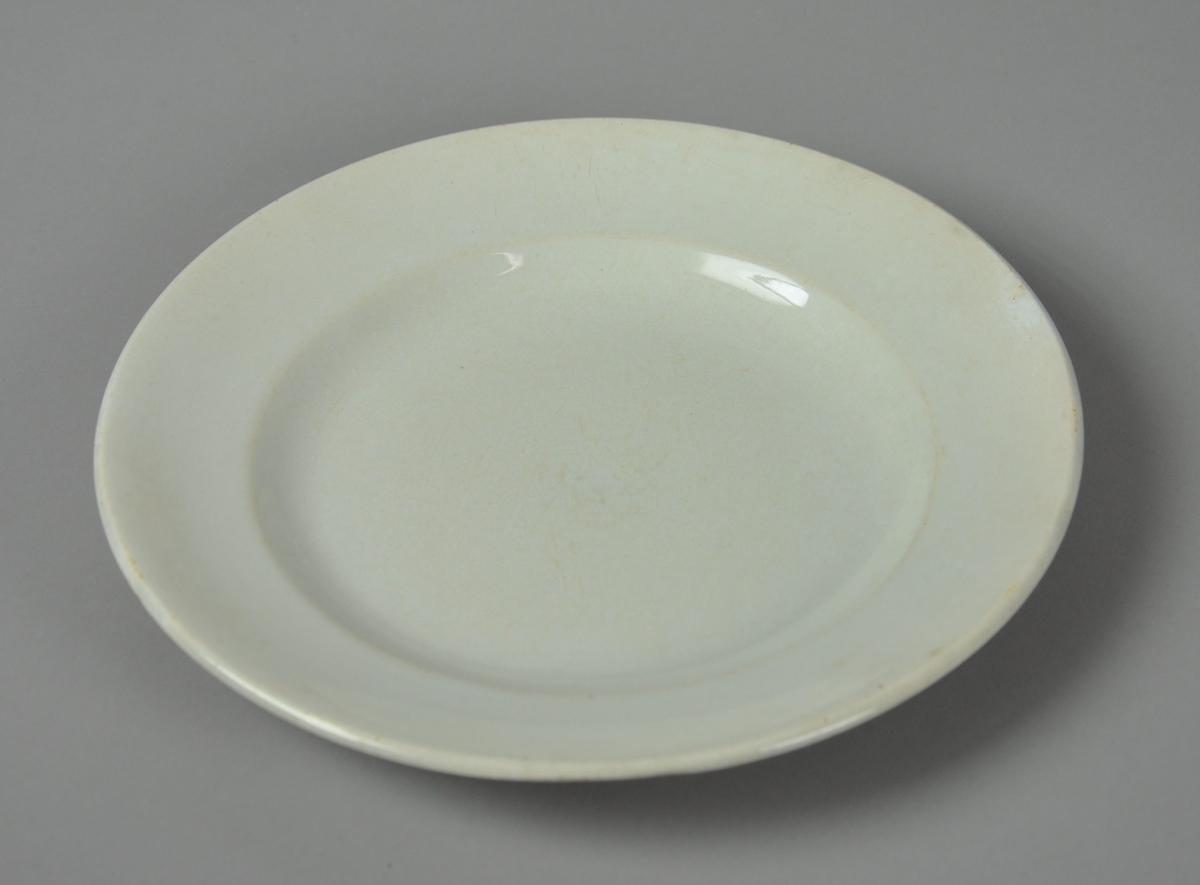 Hvit tallerken av glassert keramikk.