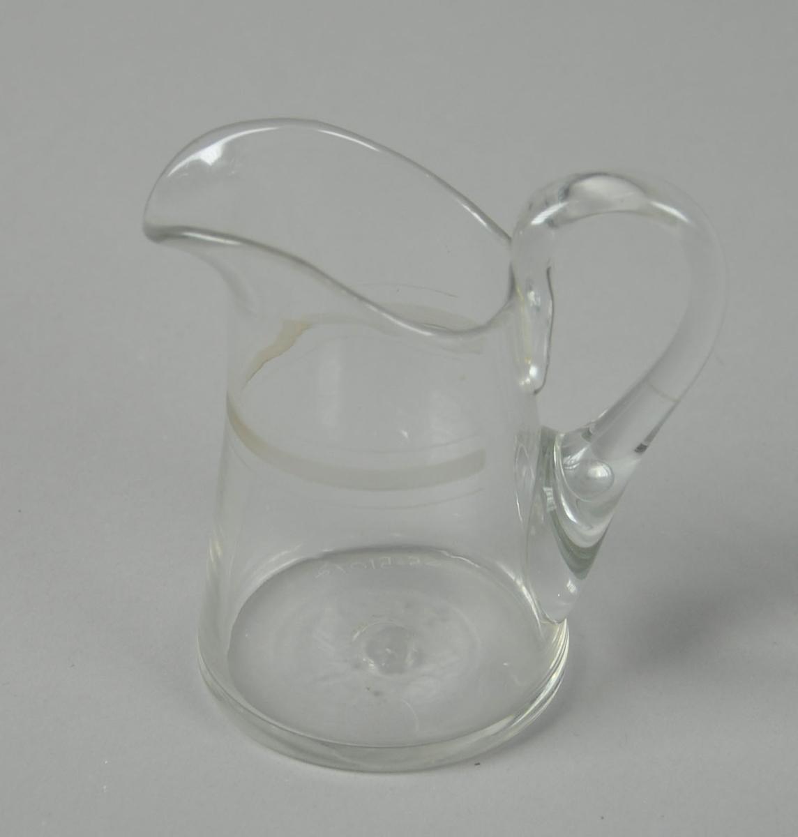 Liten mugge av glass, med hank og helletut. På utsiden av glasset er det frostede striper.