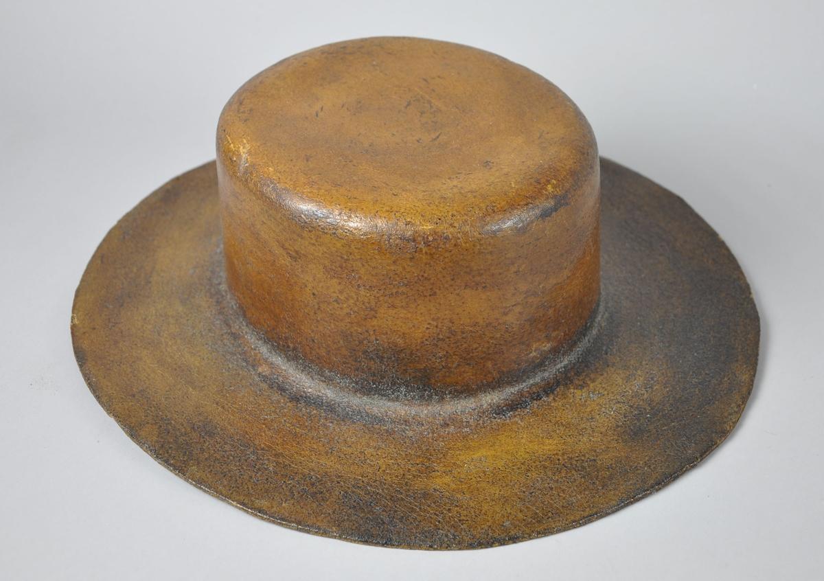Utstillingsmodell for herrehatt med brem. Hatten er brunlakkert på utsiden. På innsiden er filten lys brun/beige.