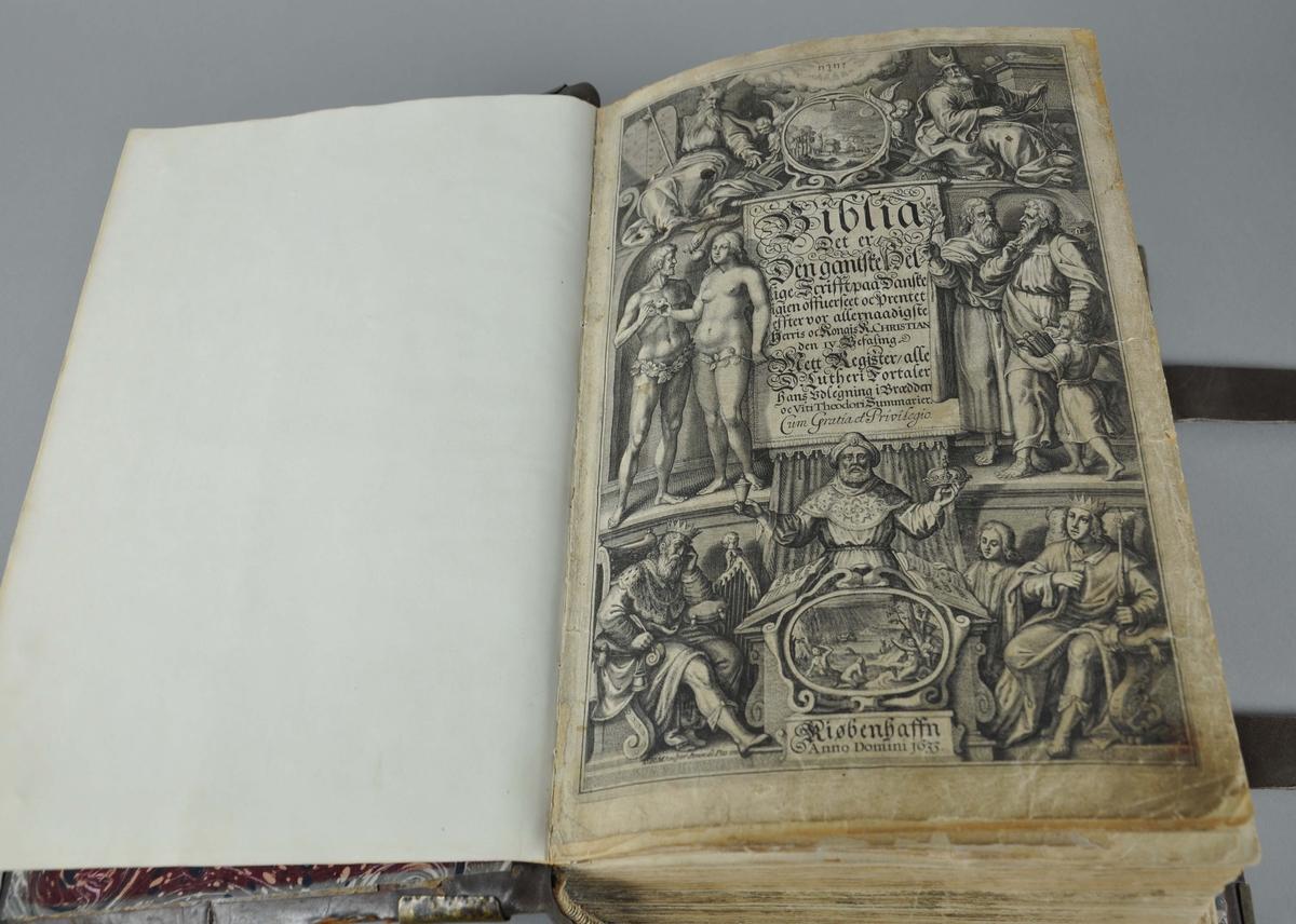 Bibel med brunt omslag av skinn. Bokomslaget har beslag av messing i hjørnene, og to festereimer av skinn.