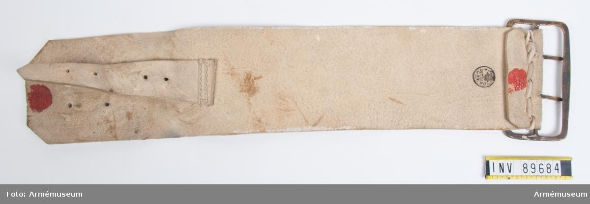 Kortare delen av en bandolärrem m/1757 av vitmålad sämsk med mässingsspänne. Den mindre remmen är tänkt att fästas i patronväskan. Remmen är tillverkad av Ditzinger och har röda lacksigill vilket visar att det är ett modellexemplar.