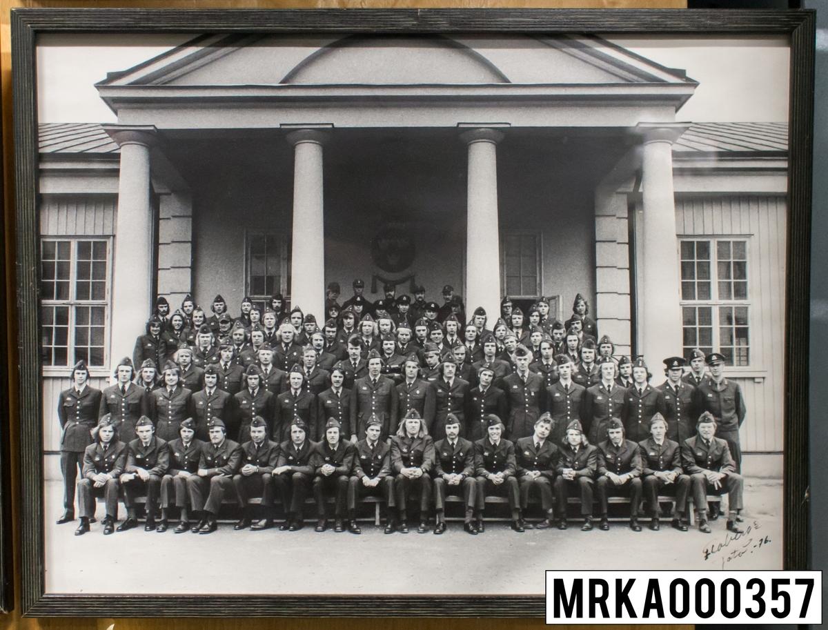 Fotografi taget på befäl och soldater som genomfört grundläggande soldatutbildning på 1:a Batteriet KA 2. Fotografiet taget utanför gymnastiksalen Gräsvik KA 2. Flobergs Foto 1976.
