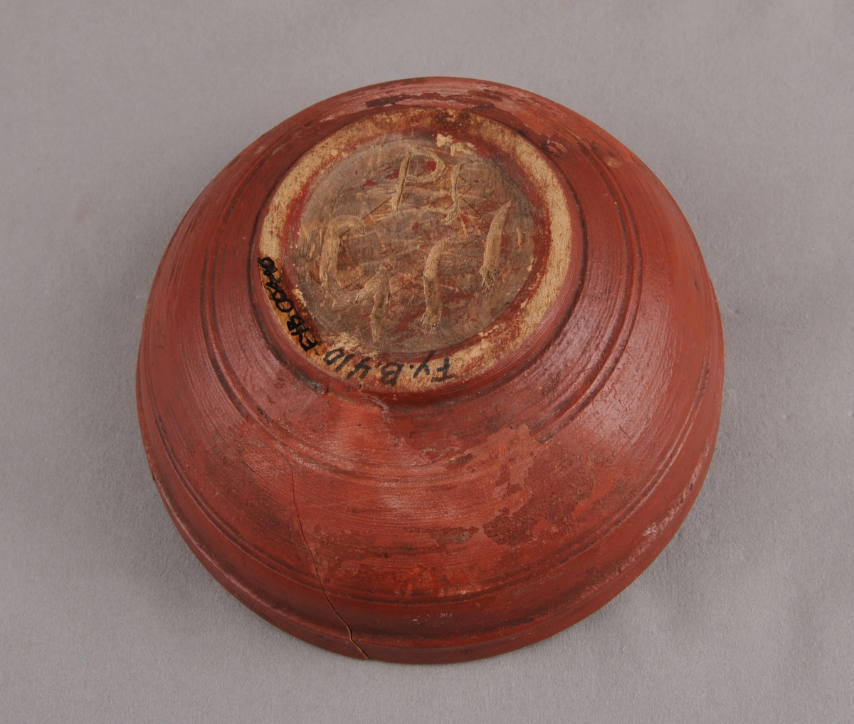 Liten bolle, dreia og måla i ein raudbrun farge. Dekorert med dreia pyntesirklar både utvendig og innvendig.