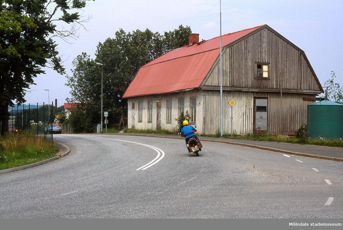 En motorcyklist passerar tingshuset i Kärra, Mölndal, år 1985. Fotografiet är taget före rivningen av byggnaden.