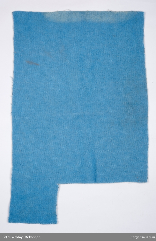 Rektangulært pleddstykke, med et avklippet stykke på den ene kortsiden, på 12 x 27 cm