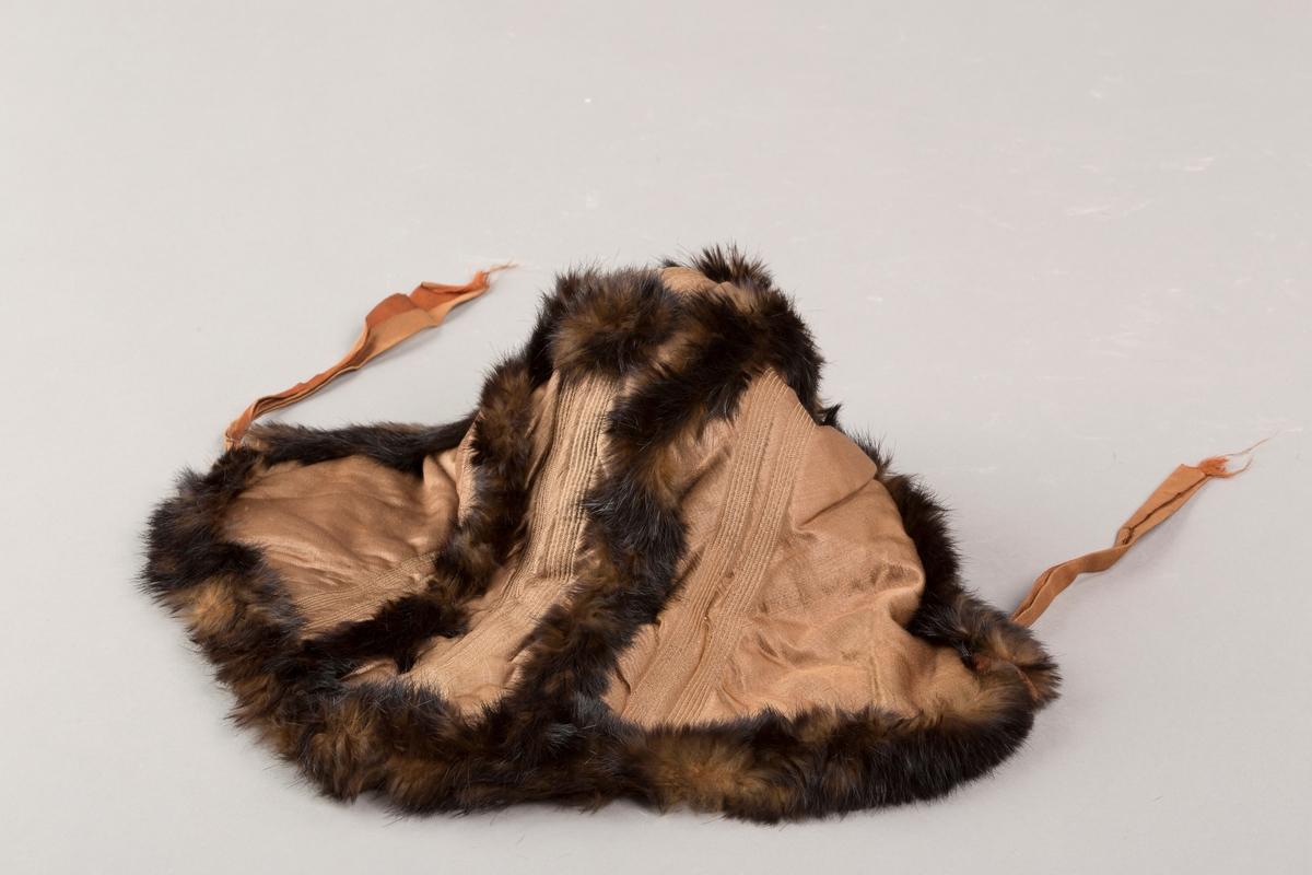 Foret, vattert silkehette med pelsbesetning. Knytebånd av silke, foret med bomull.