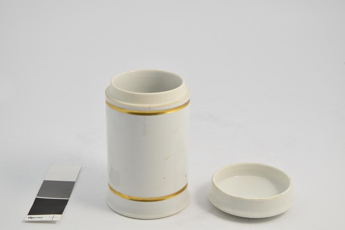 Sylinderformet porselenskrukke med porselenslokk. Hvit med gulldekor linje langs toppen og bunnen. Påtrykket dermogenum, som er en hudsalve. Krukken ble brukt til oppbevaring av hudsalve.