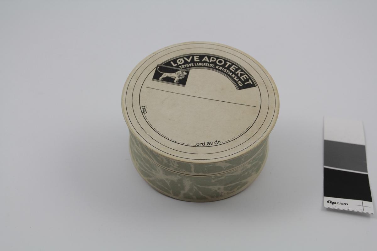 Sirkelformet eske med lokk, av papp, grå. Brukt til piller og dosert pulver.