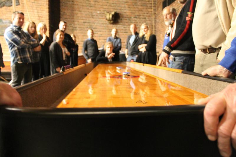 Shuffleboard i vestibylen på Norsk Maritimt Museum, nærbilde av den ene enden, mange folk rundt.