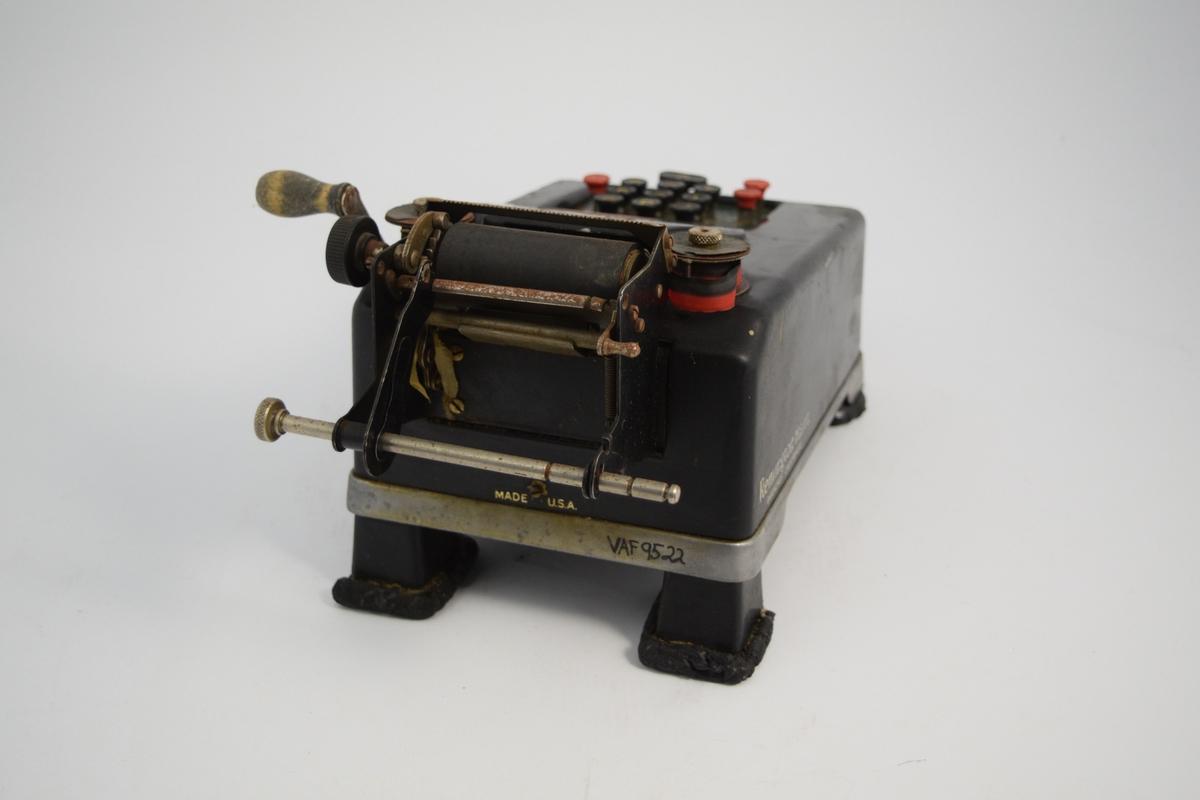 Renington regnemaskin, manuell. Rulle for papir, sveiv, tastatur, spoler for fargebånd (sort og rødt). Sortlakkert metall. Håndtak på sidene ble brukt til addering. Brukt til summering på apotek.