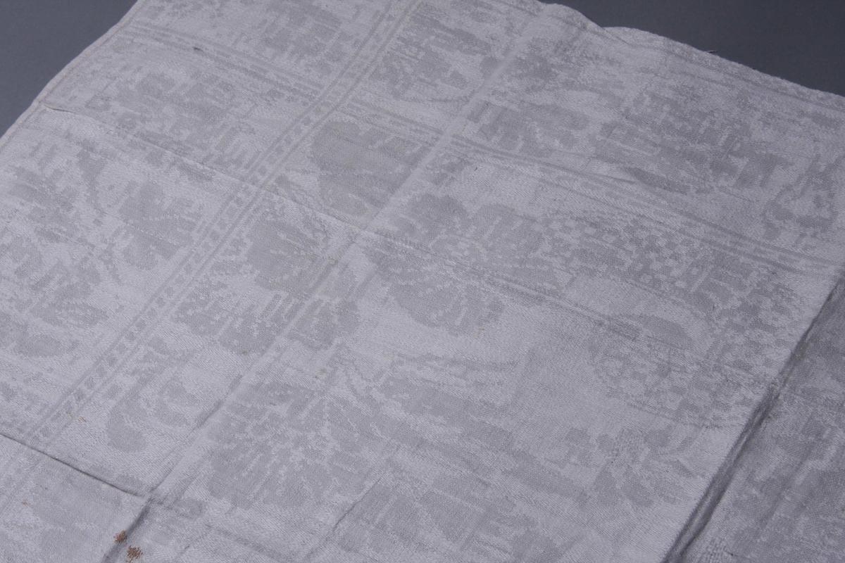 Hvit lindamask med stilisert blomsterbord langs kanten mellom to smalere stripeborder. Smal fall på kortsidene og monogram: BM, speilvendt.