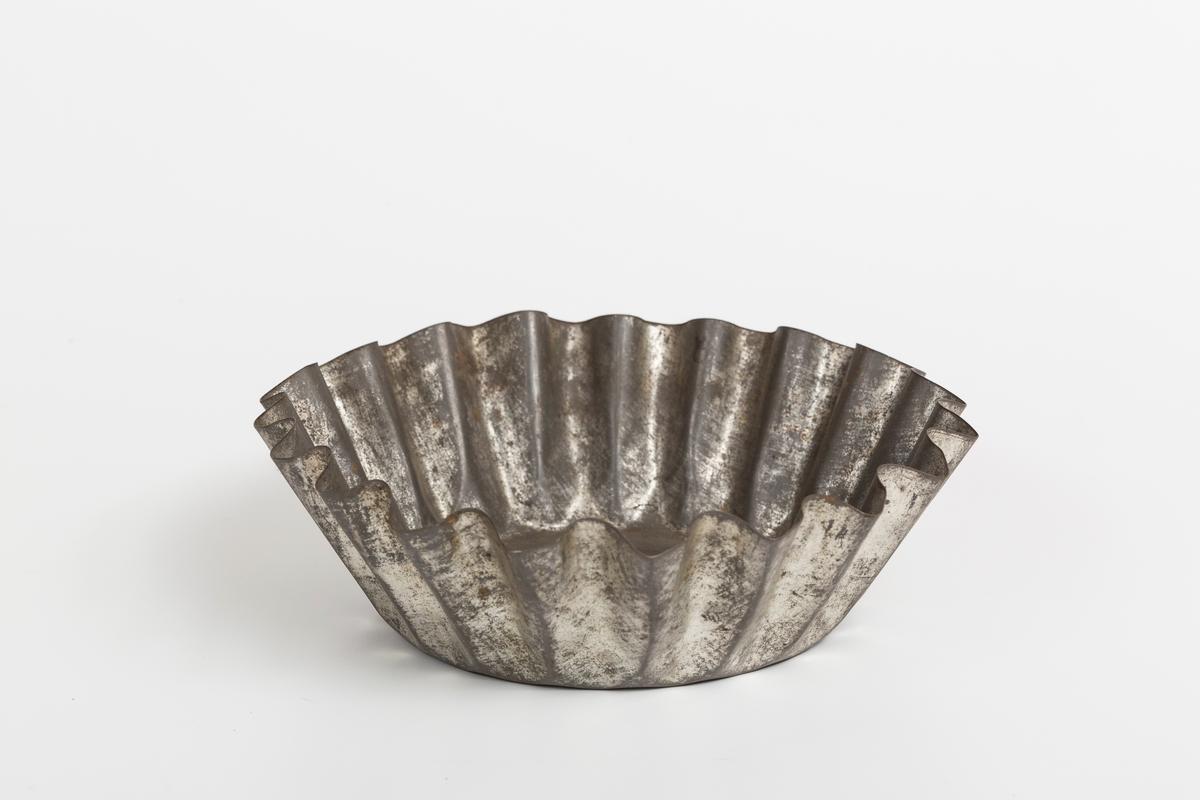 Kakeform for terte, også kalt terteform. Blomstdekor på bunnen av formen. Noe rust på formen.
