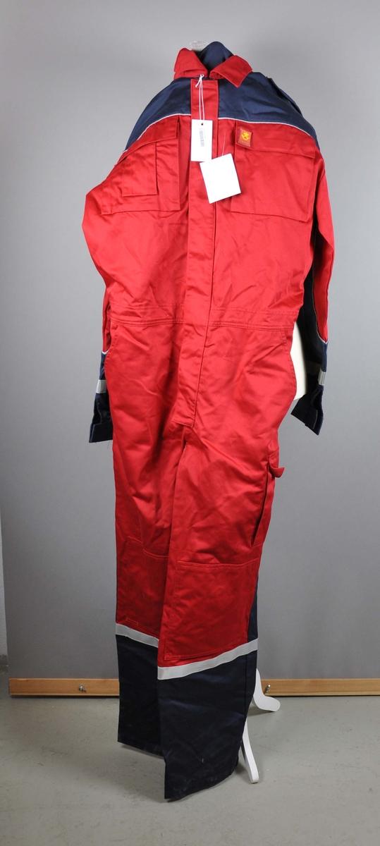Rød uniformskjeledress med postlogo.  Strikk i livet. 6 lommer + mobillomme. Reflesbånd på ermer og ben. Skulderklaffer med knapp med posthorn.