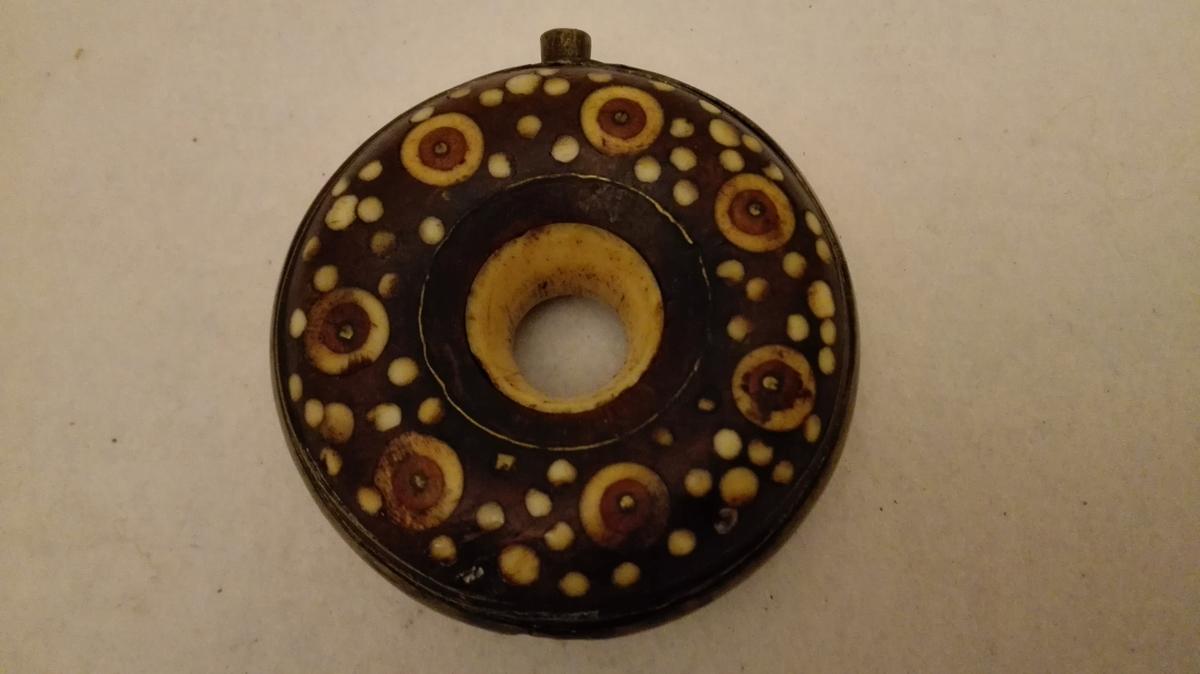 (3 snusflasker)  4286: Liten ringformet dreiet snusflaske. Siderne forsiret med indlagte større og mindre runde benplater. I hulet i midten indlagt en dreiet benring og rundt ydre kant en messinggjord, i hvis øvre ende en rørformet tut. Noget defekt. Diameter 6,9 cm. Tykkelse 2,7 cm.