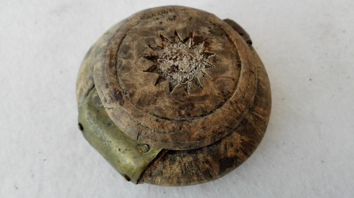 2 snusdaaser.  Runde, dreiete flattrykte snusdaaser av ri-ved (birk?) Den ene har trælaag, hvori har været indfældt en metalstjerne, paa den anden er laaget borte. I bunden har i horn været indfældt en messingplate, der mangler paa den ene. Paa denne er indgraveret: E.H.S.I. 1858. Gave fra omstreifer Axel Larsen, Askevold.