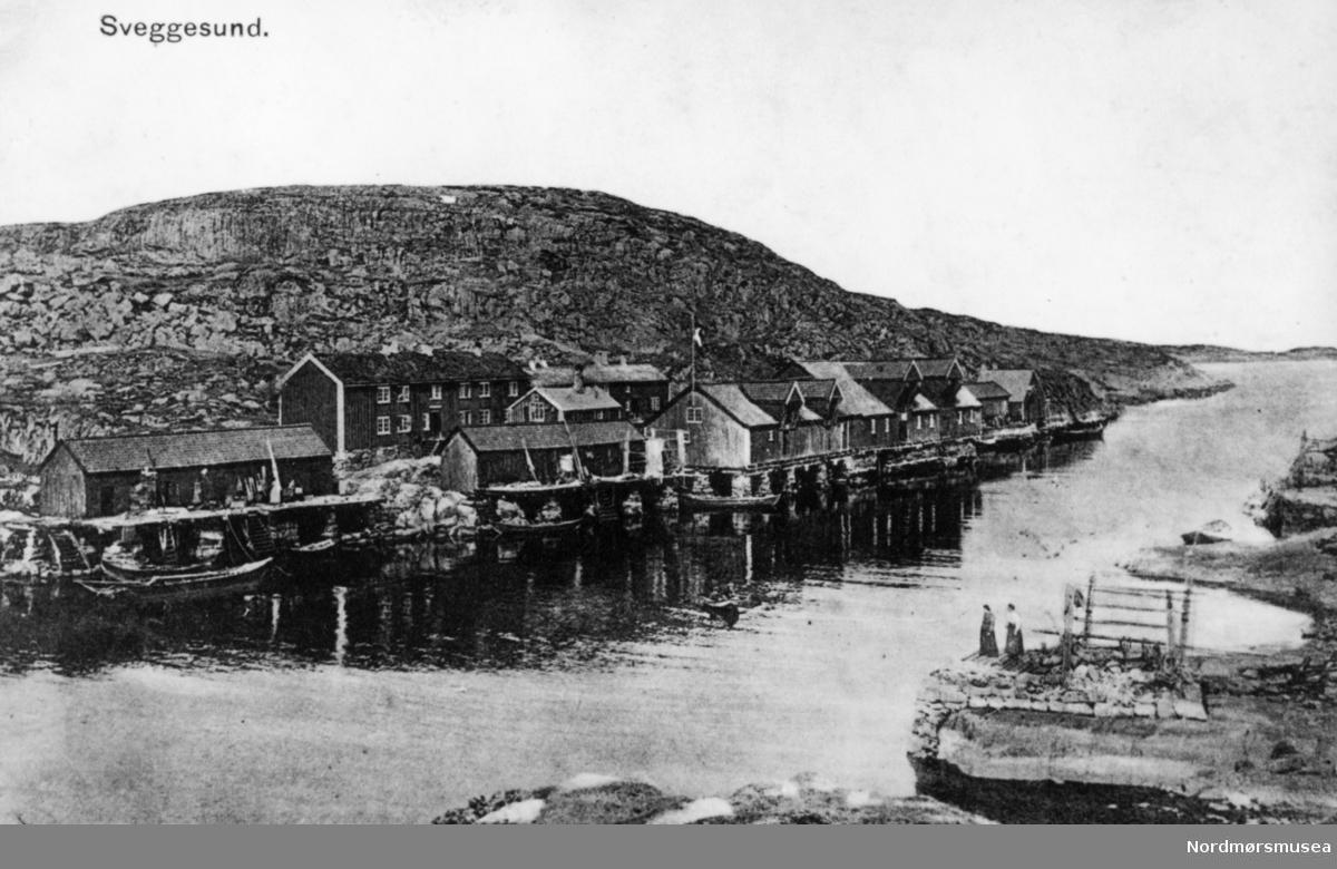 Foto fra Sveggen i Averøy kommune. Datering er trolig omkring 1920-1939. tørrfiskhjeller?  Sveggen er et gammelt fiskevær lokalisert helt på nordspissen av Averøy. Været ligger i et sund, Sveggesundet, i le - men også helt opp mot leia. Sveggen har vært kjent som ei god havn for sjøfarende opp gjennom tidene, og nordlandsjektene som fraktet fisk sydover til Bergen (ca. 1500 - 1900) brukte ofte Sveggen som natteleie fordi de ikke kunne seile når det var mørkt. I Sveggen er det også gode hamneforhold under storm og uvær.  Sveggen blir nevnt første gang i Snorre Sturlassons kongesagaer i 1040 når Magnus den Gode lå til ankers her natten før han skulle til møtet i langøysund. Fra Sverres saga nevnes stedet i 1204 da birkebeinerne og baglere søkte å komme i strid her, og i 1206 lå baglerhøvdingen Erling Steinvegg her med flåten sin. I 1537 når Nidaros siste katolske erkebiskop flyktet mot Holland ankret han opp i Sveggen på sin ferd sydover. På hollandske sjøkart fra 1600-tallet kan vi finne Sveggen avmerket som havn.  Sveggen som havn nevnes i ulike kilder over en periode på tusen år. Dette gir oss et tydelig bilde av Sveggen som en god havn. Men Innseilingen til sundet er farlig. I 1666 forliste 6 båter under skreifiske i en voldsom landvindsstorm med snøkav, og 48 mann omkom. Kirkebøkene forteller om mange tragedier utover 17- og 1800-tallet hvor uttallige fiskere mistet livet på havet.  Fiskere var i stor grad husmenn som eide husene sine selv, men var forpliktet til å levere all fangst til landherren. Dette var ofte spire til krangel og strid. Først i 1909 fikk folket i Sveggen kjøpe grunnen de bodde og arbeidet på, men de måtte vente helt til 1942 til alle klausuler som innbefattet salg og utnyttelse av eiendommene som rett til handel og leveringsplikt. Først da kunne fiskerne selge fisken sin til de som betalte mest.  I eldre tider var det skipstrafikken som stod for all samferdsel mellom by og land og øyer her ute. For å komme seg over sundet måtte man ty til ege