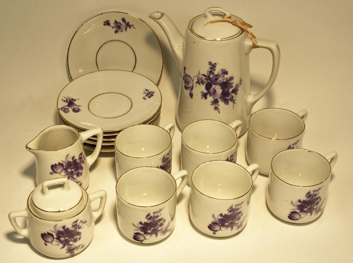 """En leksaksservis (""""dockservis"""") bestående av en kaffekanna, en sockerskål, en gräddkanna samt 6 koppar med fat. Tillverkad av vitt fältspatsporslin med blå, tryckta blommor som dekor, samt guldrand på samtliga delar. Helt omärkt. Något kantstött. Kannans höjd; 145 mm, söckerskålens höjd; 70 mm, gräddkannans höjd; 60 mm, koppens höjd; 55 mm, fatets diameter; 112 mm."""
